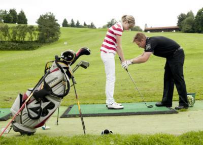 Golfpro mit Schüler