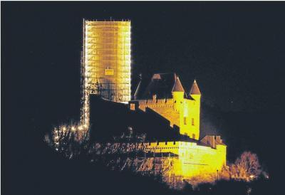 Foto zur Meldung: Ortsgemeinde: Eingerüsteter Bergfried leuchtet in der Nacht