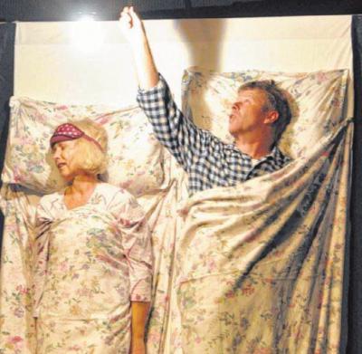"""Sketche aus dem alltäglichen Leben wurden am Wochenende im DGH präsentiert. Hier liegen Mann (Sepp Biggel) und Frau (Andrea Syska) im Bett und diskutieren über das Programm beim """"Kulturigen""""."""