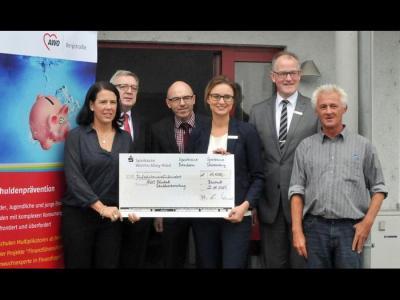 Vier Vertreter der Sparkassen Starkenburg, Worms-Alzey-Ried und Bensheim überreichen der Schuldnerberatung der AWO ihre Spende.