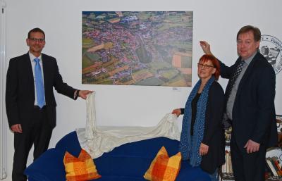 Unser Bild zeigt während der Enthüllung der Luftaufnahme von Sterbfritz v.l.n.r.: Bürgermeister Carsten Ullrich, Einrichtungsleiterin Ute Callsen und Fotokünstler Axel Haesler
