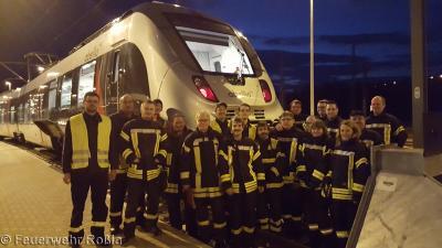 Feuerwehr Roßla vor einem Zug von Abellio