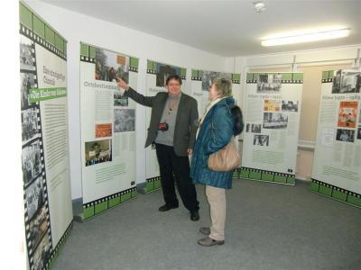 Barbara und Winfried Junge vor Rollups der Wanderausstellung in Golzow