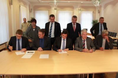Bürgermeister Fischer (Mitte) beim Unterzeichnen des Positionspapieres