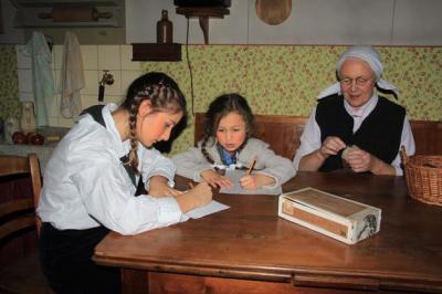Bärbel (Paulina Biggel), Lina (Emilia Biggel) und Oma Frieda (Hildegard Seel) sind am Küchentisch beschäftigt, bevor eine Hausdurchsuchung sie nach draußen treibt. Mit Emilia Biggel und Hildegard Seel sind gleichzeitig auch die jüngste und die ält