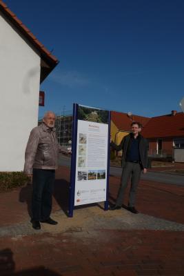 Ortsvorsteher Bernd Müller und Bürgermeister Marco Beckendorf an der Stele der AG Historische Dorfkerne