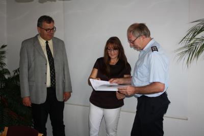 Innenstaatssekretärin Katrin Lange übergibt im Beisein von Bürgermeister Stefan Freimark den Förderbescheid an den Ortswehrführer Dietmar Leisner