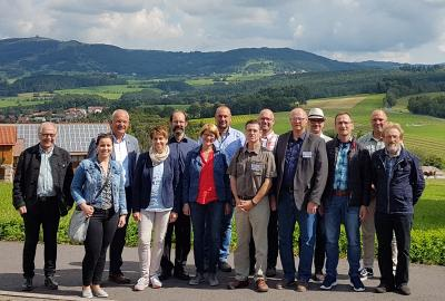 """Die Bewertungskommission mit den Ortsvorstehern und dem Bürgermeister vor der Gebietskulisse vom Biergarten des Berggasthofes """"Zur Ebersburg"""""""