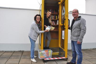 Bestückten gemeinsam die Bücherzelle (v.li.): Beate Fenz, Simone Baumann und Reiner Beck. Foto: Bulmare GmbH