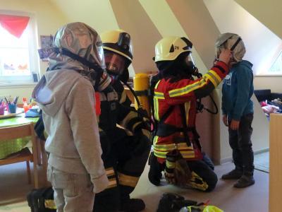 """Feuerwehrleute unter Atemschutz """"retten"""" die """"vermissten"""" Kinder bei der Übung   (Foto: F. Hinrichs)"""
