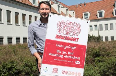 Jens Mörsel, verantwortlich für das Bürgerbudget, präsentiert das Werbeplakat für das Bürgerbudget 2019