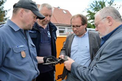 Sprengmeister Schwitzke, Stadtwehrführer Meyer, Bürgermeister Meger und Bürgermeister Garn mit einem Splitter der amerikanischen 250-Kilo-Weltkriegsbombe (v. l.)