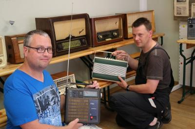 Matthias Nerenz (links) und André Bareinz vom Heimatverein Calau e.V. bauten in diesen Tagen schon einige Teile der Sonderausstellung auf. Zu sehen sind dabei auch historische Rundfunkgeräte und Fernseher. Foto: Stadt Calau