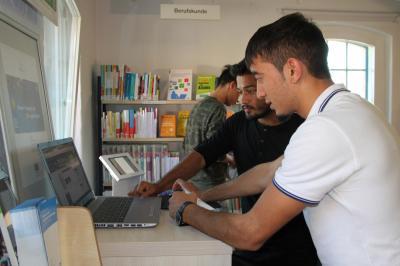 Muneer Ahmad Naraiwall (vorn), Zaki Qambari und ein Freund aus der 10. Klasse der Spreeoberschule informieren sich über ihre Chancen