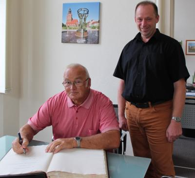 Foto zu Meldung: Rolf Lehmann trägt sich ins Ehrenbuch ein