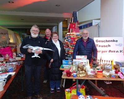 Beim Geschenkemarkt gab es alles, sogar kleine Dinos, im Hintergrund ein Christbaum aus Büchern, von links: Horst Gaul, Herbert Schwarz, Edit Gaul und Hermann Bing vom Bürgerbusverein