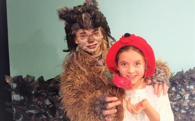 Der Wolf will Rotkäppchen überreden, einige Blumen zu pflücken - Theater für die ganze Familie