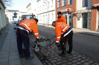 Drei Mitarbeiter der Firma Bartsch reinigen im Auftrag der Stadt die Parktaschen in der Gartenstraße.