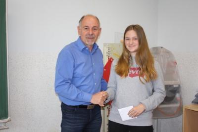 Schulleiter Uwe Schwanz dankt der Schülerin Helena für ihr Umweltengagement