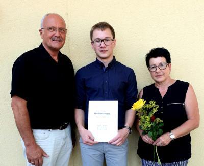 Der neue Verwaltungsfachangestellte David Wagner mit seiner Mutter und Bürgermeister Manfred Helfrich am Tag der Zeugnisübergabe vor dem Kolpinghaus Hünfeld.