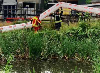 Foto zur Meldung: Ölspur in der Ortsdurchfahrt – Feuerwehr sichert das Regenrückhaltebecken