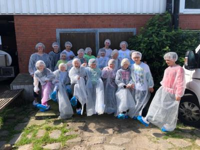 Die Gruppe des Jugendzentrums Eggebek/Langstedt mit Schutzanzügen vor der Backensholzer Käserei