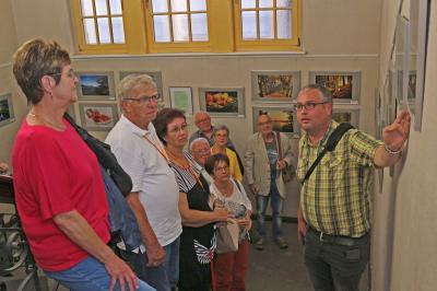 """Matthias Nerenz (rechts) ist einer der acht Fotografen der AG """"FotoGen"""" des Heimatvereins, die derzeit im Calauer Rathaus ihre Fotografien zeigen. Er erläuterte seine Aufnahmen den neugieren Besuchern der Vernissage. Foto: Stadt Calau / Jan Hornhauer"""