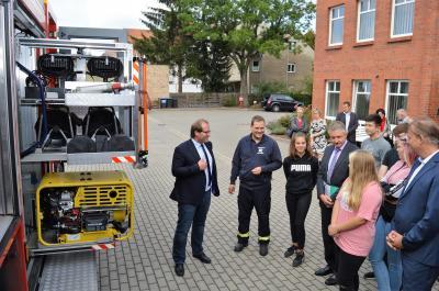 Minister Schröter (4. v. l.) brachte nicht nur einen Spendenscheck mit, sondern überzeugte sich auch vor Ort vom neuen Feuerwehr-Unterricht in Nauen.