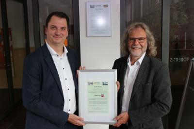 Spreegas-Geschäftsführer Andreas Kretzschmar (links) überreicht Bürgermeister Werner Suchner das Zertifikat für die Belieferung mit klimaneutralem Ökogas. Foto: Stadt Calau