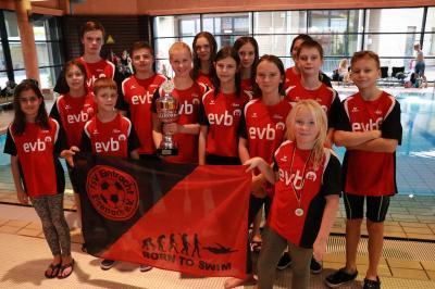 Emily, umringt von der Mannschaft, hält den Pokal in ihren Händen.