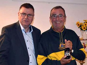 Rolf Hojnatzki überreicht dem Referenten Gerd Aschoff (rechts) zum Abschluss ein einbeck-typisches Geschenk. Foto: Einbecker Morgenpost