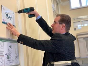 Bau-Dezernent Wilfried Brödno brachte das Hinweisschild im Landratsamt in Senftenberg im Bereich der Sitzungssäle an. (Foto: Landkreis/Werner)
