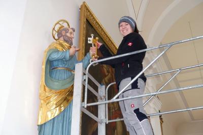 Foto zur Meldung: Tanja Preuß vergoldet einen der Petrusschlüssel und stellt somit die Richtigkeit der Ikonographie in der Pfarrkirche St. Georg Prackenbach her