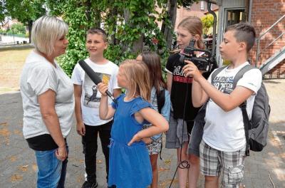 In drei kleinen Trupps ziehen die Kinder durch das Dorf Groß Laasch an die Stätten ihrer Erinnerungen. Dabei kommen sie auch an Susanne Liedtke (l.) nicht vorbei, die für die Mädchen und Jungen eine wichtige Bezugsperson ist. Thorsten Meier