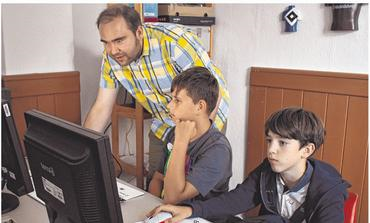 Lernen, wie mit dem Computer umgegangen werden muss: Julian (l.) und Paul (r.) folgen den Anweisungen von Kursleiter Daniel Piasecki.