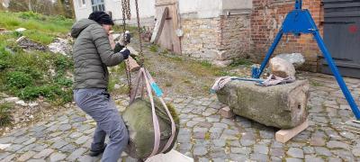 Cathrin Bothmann mit der Steinkugel vom Edelmannsgrab, daneben der Schaft des stark ramponierten Meilensteins.