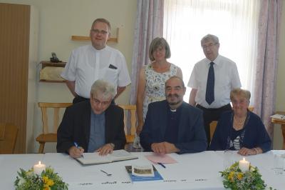 Foto zur Meldung: Domkapitular Prof. Dr. Josef Kreiml trägt sich ins Goldene Buch der Pfarrei Prackenbach ein
