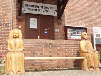Die beliebte Bank mit Starka und Starki/Oma und Opa steht wieder vor dem Heimatmuseum und lädt zum Verweilen ein.