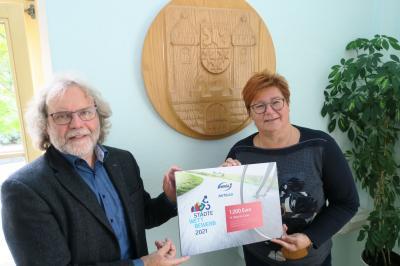 Simone Erb, Mitarbeiterin von enviaM, überreichte den symbolischen Scheck an den Calauer Bürgermeister Werner Suchner. Foto: Stadt Calau / Jan Hornhauer