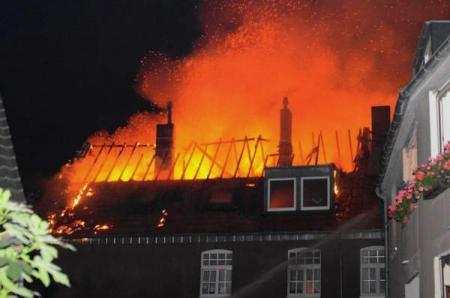 Flammen schlagen aus dem Dachstuhl des Reihenhauses(Quelle: Miklos Laubert www.bf-koeln-einsaetze.de)