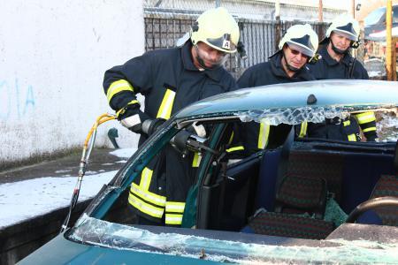Einsatzkräfte der Ortsfeuerwehr Gütz beim Aufschneiden eines Übungsautos