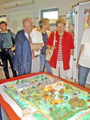 Bürgermeister Peter Schauer betrachtet das von den Kindern erstellte Modell ihres Traumschulhofes