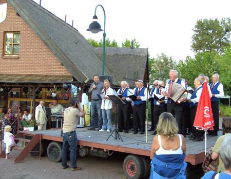 Der Männerchor, der Sänger Muck und Bürgermeister Willi Voß singen gemeinsam am 31.7.2009 am Hafen das Mecklenburg-Lied