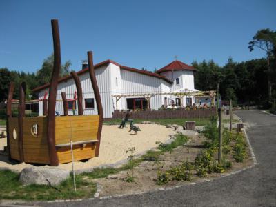 Erlebnisspielplatz mit Restaurant im Hintergrund
