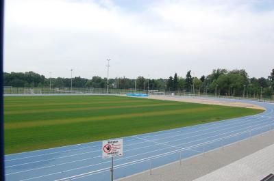 Blick über das Rasengroßspielfeld auf die Weit- und Hochsprunganlage und die blaue Laufbahn. Im Hintergrund: Die Kunstrasenplätze.