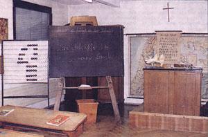 Klassenzimmer um 1900: Rechenschieber, Schreibpult, Schiefertafel und das erhöhte Lehrerpult