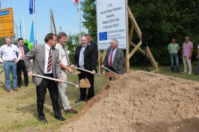 Bild der Meldung: Bürgermeister Klaus Ahrens greift beim Baustart der L33 zum Spaten