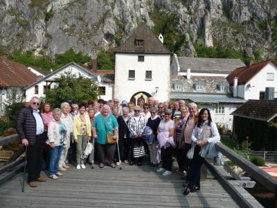 Das Bild zeigt die begeisterten Eckersdorfer Senioren vor dem gotischem Torturm Essing, hinten die senkrecht aufragenden Felswände. Rechts im Bild: Bürgermeisterin Sybille Pichl