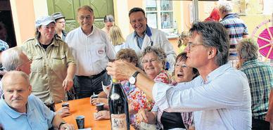Renate Gärtner, Harald Kinninger und Peter Müller (hinten v.l.) hoffen berechtigt auf einen guten Erlös für die von Peter Escher (vorn) inspizierte Schnapsflasche. Foto: Frank Schmidt