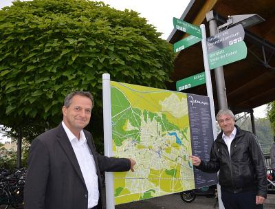 v.l.: Baudezernent Thomas Zylla und Bürgermeister Heiko Müller nahmen die neue Tafel und den Wegweiser am Bahnhof Falkensee in Augenschein.